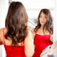 Woman trying clothing looking in mirror adjusting dress. Beautiful young multiethnic girl.
