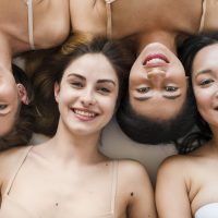 multiracial-group-cheerful-young-women-lying-back